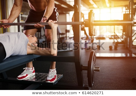 Stockfoto: Young Fit Woman Working Out With Barbell On Bench
