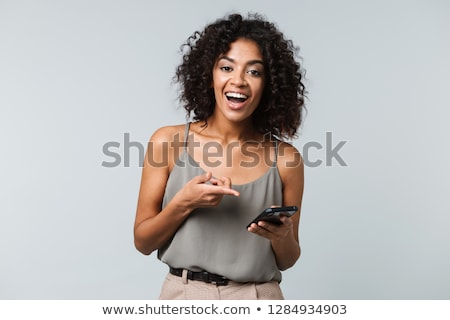 Pretty young african american woman standing and writing in notebook  Stock photo © deandrobot
