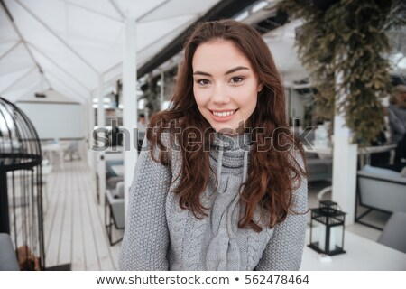 Incredible young lady dressed in sweater sitting in cafe Stock photo © deandrobot