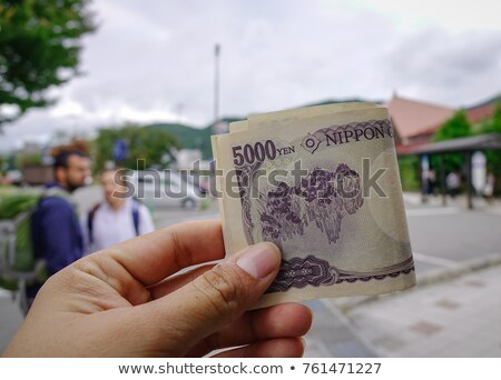 hand holding a yen currency symbol. Stock photo © alexmillos