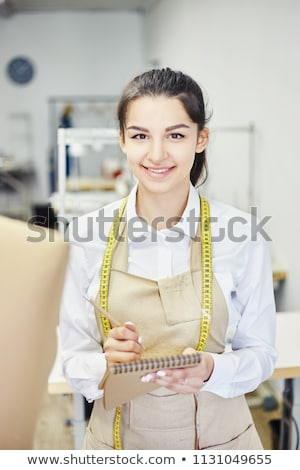 woman fashion designer holding sketchbook while standing at her studio stock photo © deandrobot