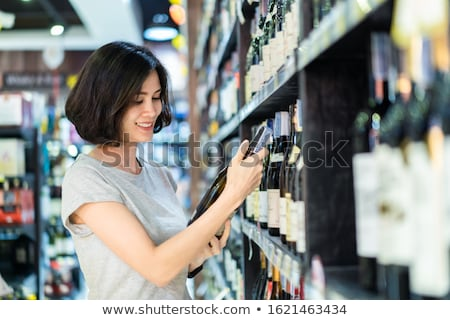 Smiling woman holding bottle of wine  Stock photo © wavebreak_media