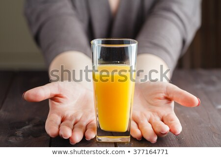 casual woman drinking juice by the table on kitchen stock photo © deandrobot