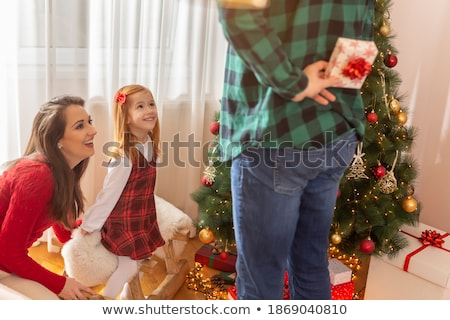 man hiding a christmas present behind back stock photo © is2