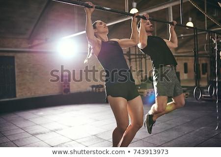 Muscular man doing pull-ups on horizontal bar Stock photo © boggy