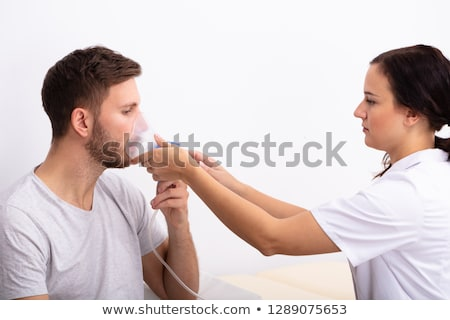 Doctor Holding Oxygen Mask Over Patient's Mouth Stock photo © AndreyPopov