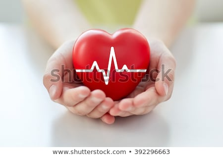 close up of hand holding red heart with cardiogram Stock photo © dolgachov