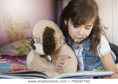 7 years old girl reading a book on bed Stock photo © Lopolo
