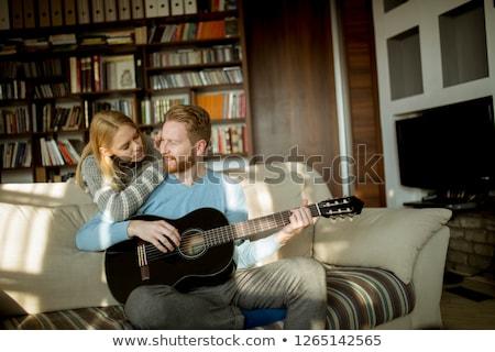 Férfi játszik akusztikus gitár kanapé fiatal gyönyörű Stock fotó © boggy