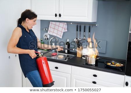 woman extinguishing burning cooking pot stock photo © andreypopov