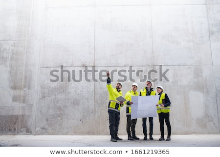 Architect standing in an empty space and holding a plan Stock photo © ra2studio