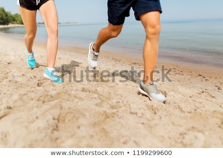 legs of sportsmen in sneakers running along beach Stock photo © dolgachov