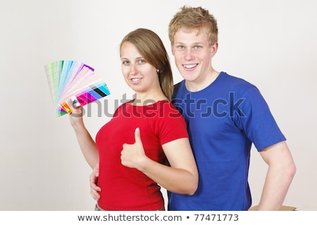Image of joyful couple man and woman holding paint rollers and b Stock photo © deandrobot