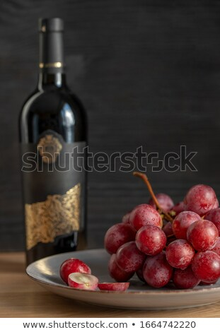 Bottle of red wine with dark grapes with corks and opener inside Stock photo © DenisMArt