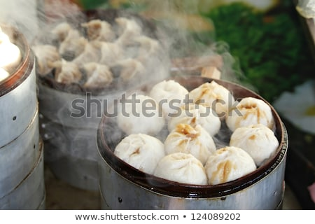 Street food booth selling Chinese specialty Steamed Dumplings in Stock photo © galitskaya