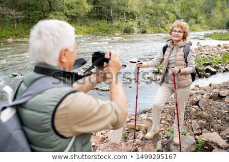 Olgun kadın trekking poz kamera koca sırt çantası Stok fotoğraf © pressmaster
