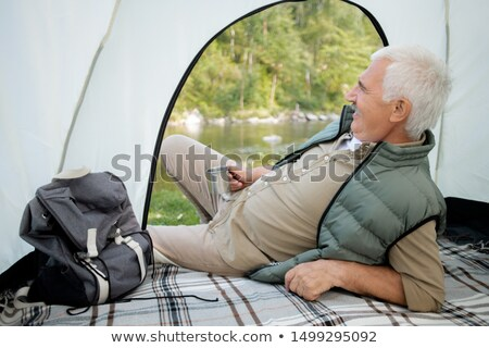 Mature restful man with hot tea lying in tent while looking at river Stock photo © pressmaster