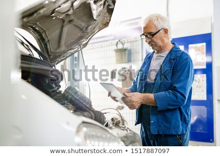 Mature man with grey hair looking at touchpad display during technical service Stock photo © pressmaster