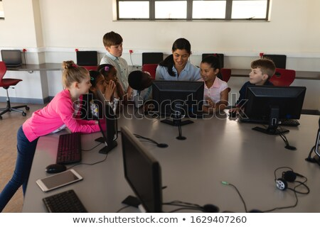 Overhead of female teacher teaching computer to schoolkids at desk in school Stock photo © wavebreak_media