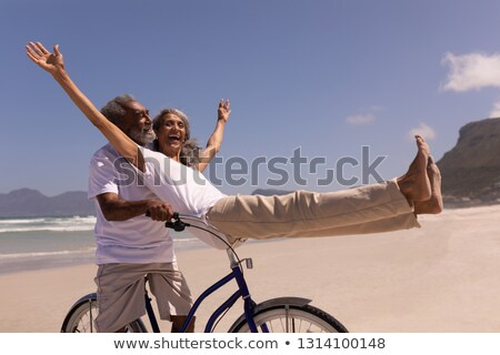 Side view of active senior woman riding bicycle at the beach with ocean in the background. She seems Stock photo © wavebreak_media