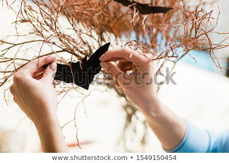 Hands of girl holding black paper bat by dry branches while decorating them Stock photo © pressmaster