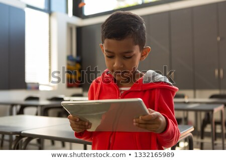 Front view of thoughtful mixed-race schoolboy using digital tablet at desk in a classroom at element Stock photo © wavebreak_media