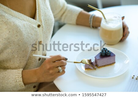 Kezek fiatal nő cappucchino eszik áfonya sajttorta Stock fotó © pressmaster
