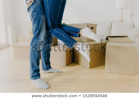 Cropped shot of caring man lifts his wife up, wears jeans and socks, just moved in new home, pose ar Stock photo © vkstudio
