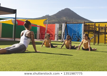 Font view of caucasian trainer teaching stretching exercise to students in school playground at scho Stock photo © wavebreak_media