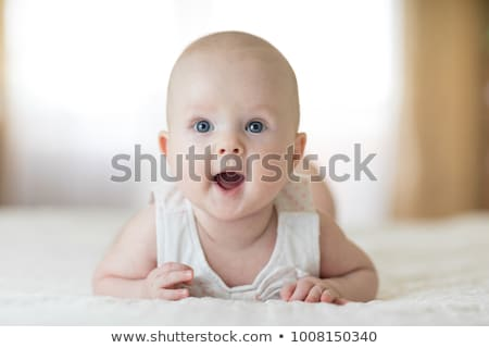 cute baby laying on belly stock photo © phakimata