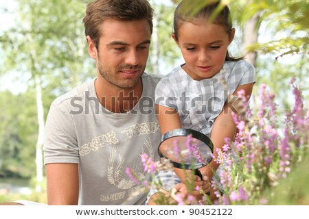 father and little daughter observing flowers with magnifying glass Stock photo © photography33