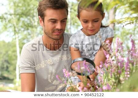 apa · kicsi · lánygyermek · virágok · nagyító · virág - stock fotó © photography33