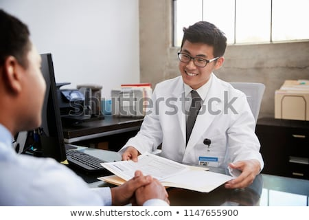 Happy young doctor in focus, two others in out of focus stock photo © get4net