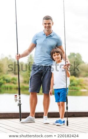 smiling little boy holding fishing rod stock photo © przemekklos