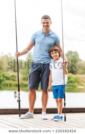Sorridente pequeno menino vara de pesca grama Foto stock © przemekklos