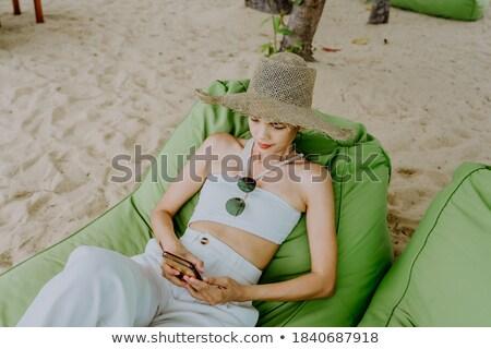 jonge · aantrekkelijke · vrouw · ontspannen · ligstoel · zonnebril - stockfoto © stockyimages