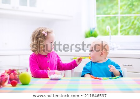 Two little sister girls eating together stock photo © lunamarina