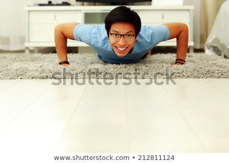 Portrait of a smiling  young man doing push ups in the living room at home Stock photo © deandrobot