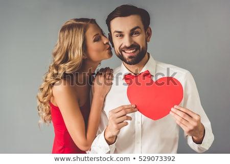 Woman kissing man as he holds heart Stock photo © wavebreak_media
