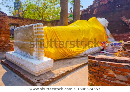 lying buddha dressed in yellow scarf in temple wat yai chai mong stock photo © meinzahn