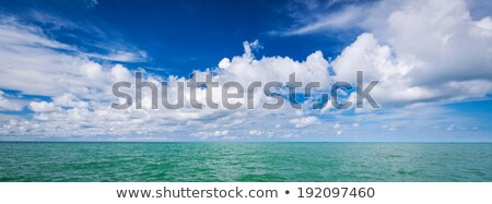 Sunset over the sea with clouds over the water surface Stock photo © stoonn