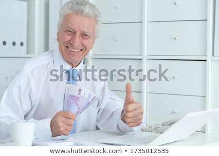 Senior caucasian doctor holding money. Stock photo © RAStudio