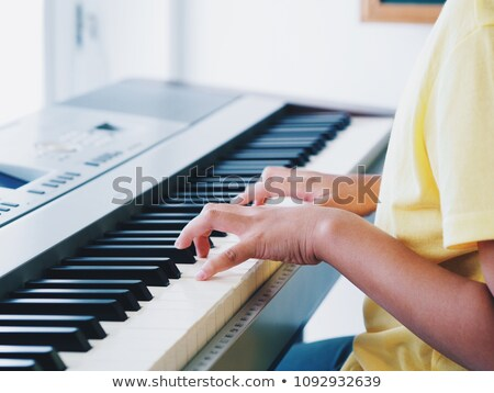 close up of boy playing piano in classroom stock photo © wavebreak_media