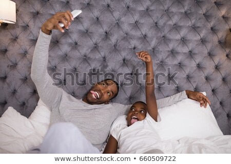 Mischievous father and son taking selfie on bed Stock photo © wavebreak_media