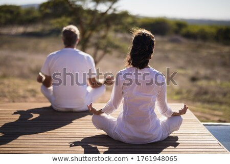 Rear view of couple practicing yoga on wooden plank Stock photo © wavebreak_media