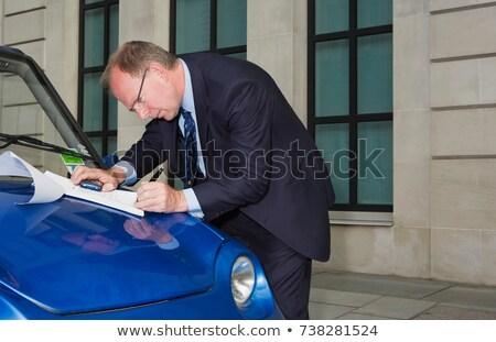Stock photo: Man signing document on car bonnet