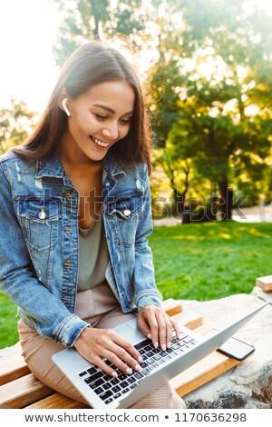 Zdumiewający pani student posiedzenia parku za pomocą laptopa Zdjęcia stock © deandrobot