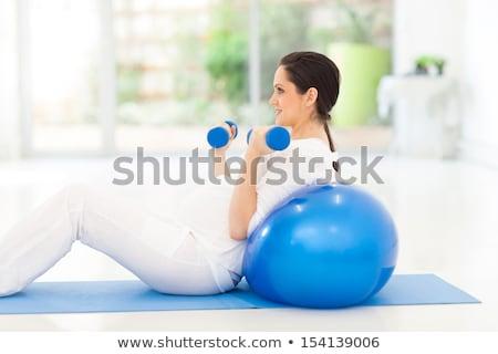 happy pregnant women exercising on mats in gym stock photo © dolgachov