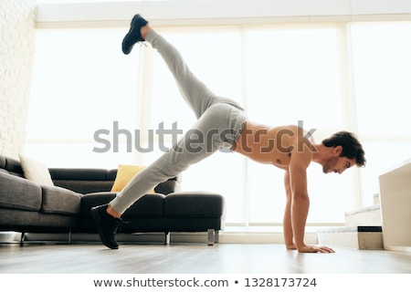 Man Training Legs and Back Muscles Doing Plank with Leg Lift Stock photo © diego_cervo