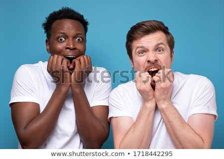 shocked young couple friends students standing isolated over white wall background pointing to you stock photo © deandrobot